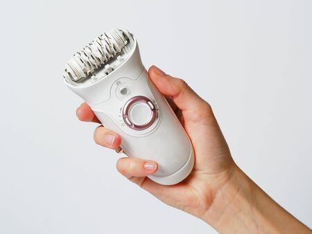 Female epilator white in a female hand on a white background. Electric hair removal device. Concept of skin care and female beauty. Women's suffering.