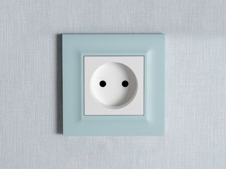 White electrical outlet with blue piping on the wall, close-up. European type sockets, the concept of construction work in the room