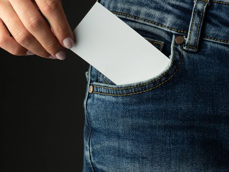 Hand of a young girl puts a business card in a jeans pocket