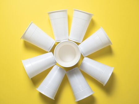 white disposable cups stand on a yellow background laid out in the shape of the sun