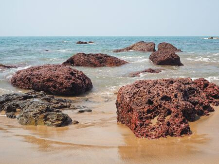 Seascape with sea, beach and red volcanic rocks. Concept of leisure and travel