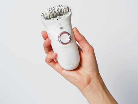 electric epilator white in a female hand on a white background. Electric hair removal device. Concept of skin care and female beauty. Women's suffering.