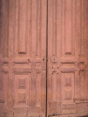 old wooden door to the monastery close up in maroon color