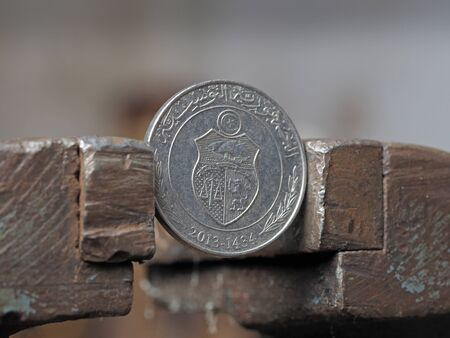 Coin one Tunisian Dinar, clamped in a metal vise, close-up. concept of financial problems and crisis. Pressure on the currency
