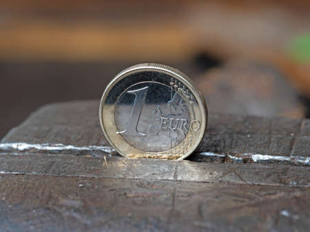 A Euro coin held in a metal grip. Concept of financial problems. Close up, top view.