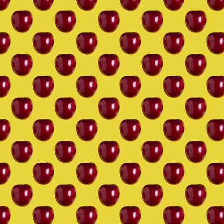 seamless pattern of juicy red cherries on a yellow background