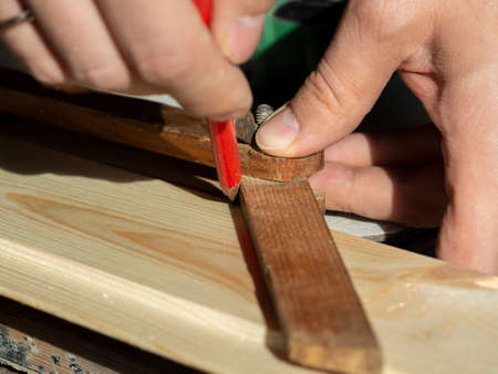 the man draws a line with a pencil on the construction Board measuring the desired angle