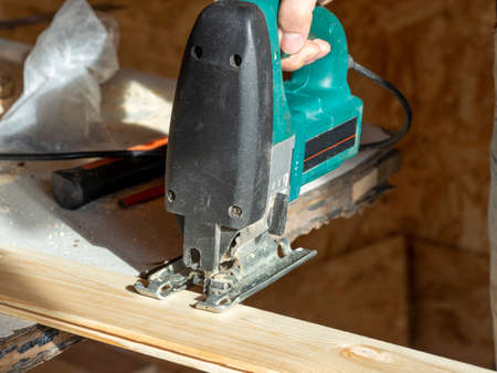 close-up of a worker sawing a wooden Board with an electric jigsaw Banco de Imagens