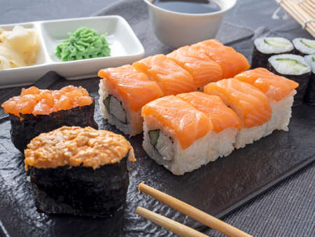 a variety of rolls and sushi gunkan nested on a black plate. next to it are bamboo wasabi sticks and sauce. Side view. traditional Japanese cuisine Banco de Imagens