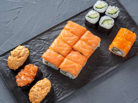 a variety of rolls and sushi gunkan nested on a black plate. Top view, flat lay. traditional Japanese cuisine