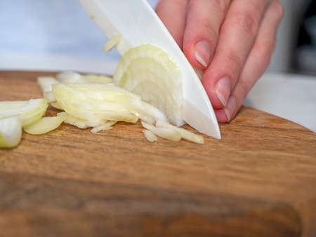 white onions are cut with a knife on a wooden Board. The concept of cooking. Selective focus.