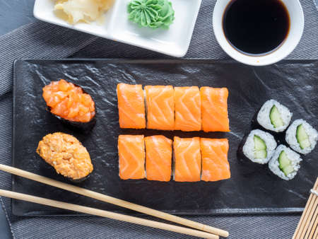 a variety of rolls and sushi gunkan nested on a black plate. next to it are bamboo wasabi sticks and sauce. Top view, flat lay. traditional Japanese cuisine Imagens
