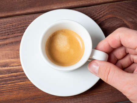 close-up of a man's hand holding a small white cup of aromatic espresso over a white saucer. Wooden background, Top view, flat lay