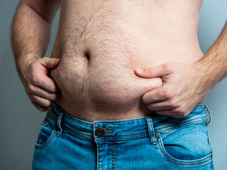 The man in jeans squeezes his hairy, flabby, fat stomach. The concept of poor nutrition. body positive. Self-acceptance