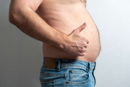 a fat man in jeans with a stomach and a finger raised in the air. The concept of body positivity. self-acceptance