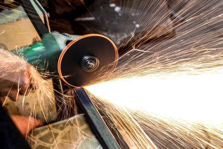 Werknemer snijden metaal met grinder. Vonkt tijdens het slijpen van ijzer