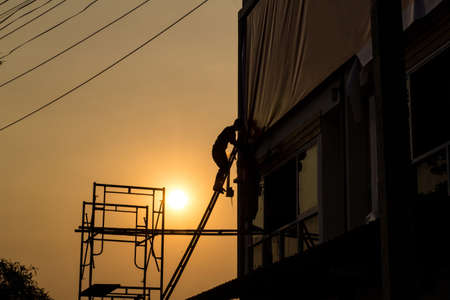 Label technician working install in sunset., silhouette style.