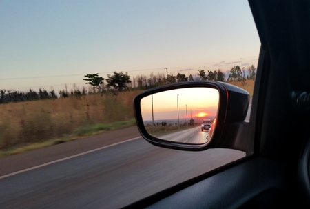 From the rearview mirror you can see the sunset on the horizon.