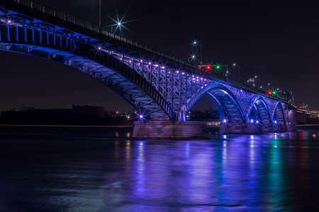 De Peach-brug die Canada met de VS verbindt in Fort Erie, paars verlicht. Stockfoto