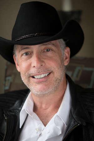 kapelusze: Mężczyzna ma na sobie kapelusz, z bliska, naturalnymi oświetlenie, uśmiechając się. Zdjęcie Seryjne