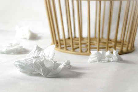 Four white used tissue paper on the white floor and trash basket on background ,selective focus on foreground.Keep clean concept. Banque d'images