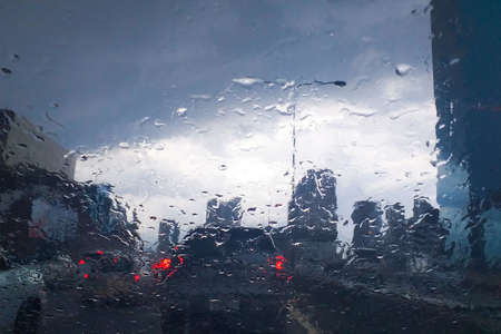 Cars on the way traffic jam after big rain storm, View from in side the car, rain drops and tears on the car windshield glass. blur pool vision.