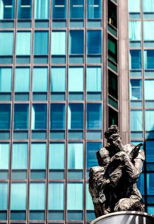 PARIS, FRANCE - August 27, 2016: La Defense, Les hommes de la Cite, The men of the City, eight Sculptures by Siptrott 1995. A crouching man in front of a skyscraper Editorial
