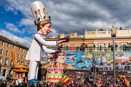 NICE - FRANCE - 03 mars 2014: Roi du carnaval 2014. Le pâtissier avance avec son énorme gâteau, offrant une tranche sur l'assiette Banque d'images - 69851336