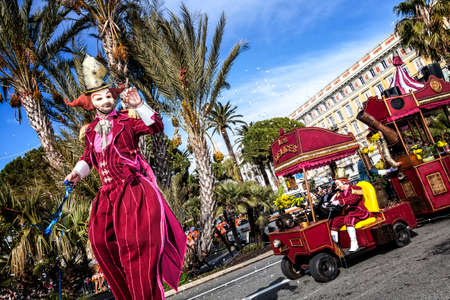 NICE - FRANCE - March 01, 2014: Carnival of Nice, Flowers' battle. A wader in red costume and a little train Banque d'images - 97176088