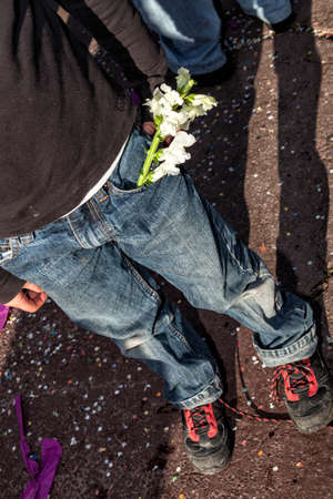A young boy with a sprig of white flowers in his pocket Banque d'images