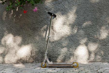 Kick scooter resting on the wall in the summer sun