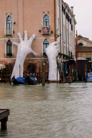 VENICE, ITALY - November 2017: Monumental hands rise from the water in Venice