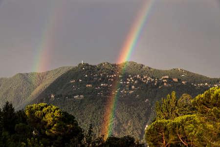 Double arc-en-ciel sur la montagne surplombant Côme. Ville de Brunate en été. Lac de Côme. Italie Banque d'images - 97244160