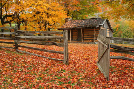 Old cabin during fall of the year with wooden fence and an open gate.