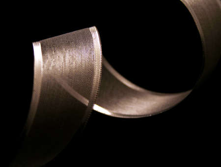 silver ribbon: Silver ribbon curled up on a black background. Stock Photo