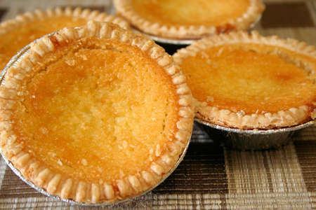 close up of home made coconut custard tarts on a place mat. Stock Photo