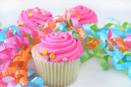 pink cupcakes on a white background with colorful ribbons laying around.