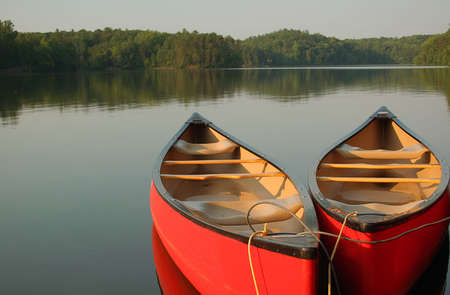 Red canoes on a calm evening at the lake photo