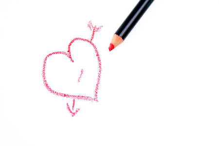 rna heart with an arrow through it drawn with a red pencil on a white background. Stock Photo