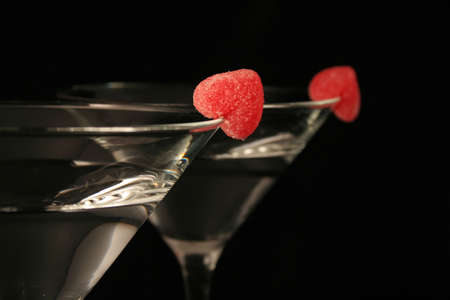 happyhour:   two martini glasses with red hearts all on a black background.