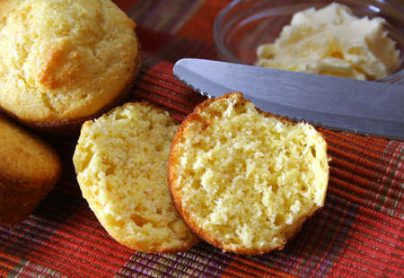 corn bread muffins with knife and butter in the background.    corn bread muffins with knife and butter in the background.   Stock Photo