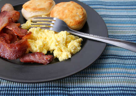 breakfast plate of eggs, bacon and biscuits photo