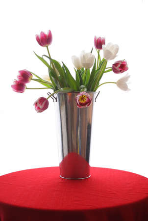 beautiful bouquet of tulips in a chrome vase sitting on a red covered table Stock Photo - 2656224