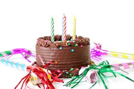 Chocolate Birthday cake with candles and noise makers on a white background.