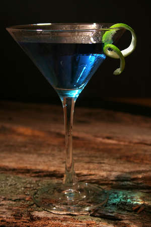 happyhour: Blue Curacao Cocktail in a martini glass with a lime rind on the side of glass. It has mood lighting, and is shot on an old piece of wood with great texture.