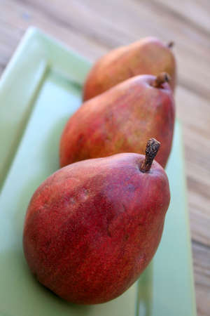 lined up: Three red pears lined up on a green oblong glass tray.
