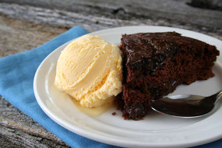 Hot fudge cake with vanilla icecream, all with a plate, spoon, and napkin.