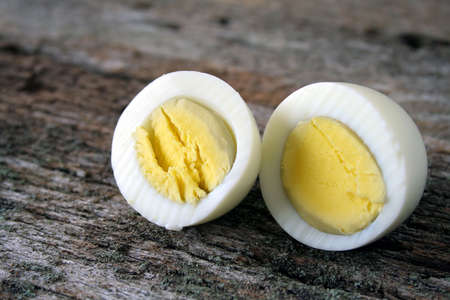 A hard boiled egg sliced in two ready to be eaten.