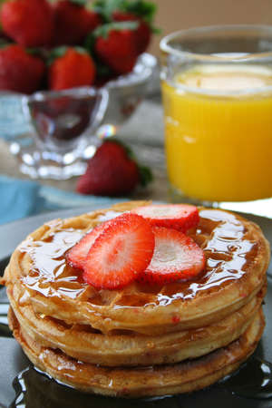 Strawberry waffles with fresh sliced strawberries and syrup. In the background there is OJ and fresh strawberries.