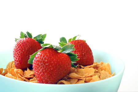 Bowl of cornflakes with fresh strawberries on top in a blue bowl isolated on a white background. photo